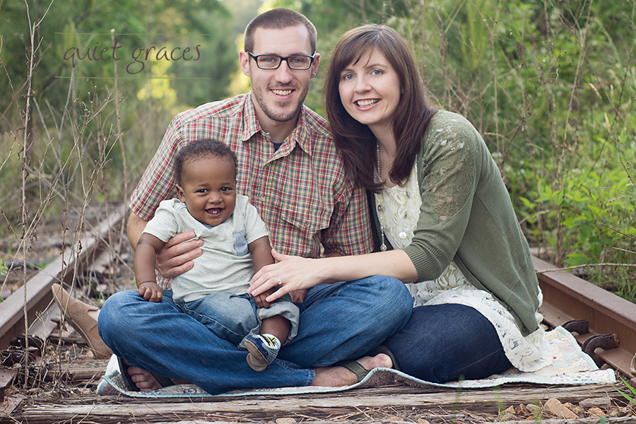 Greenville SC Baby Photography Family portrait on unused railroad tracks with giggling adopted baby