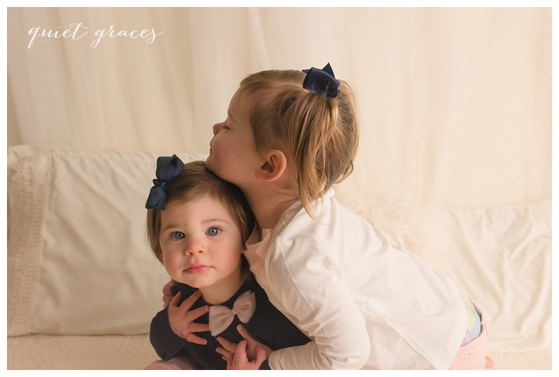 Sisters on a bed photographer studio greenville sc